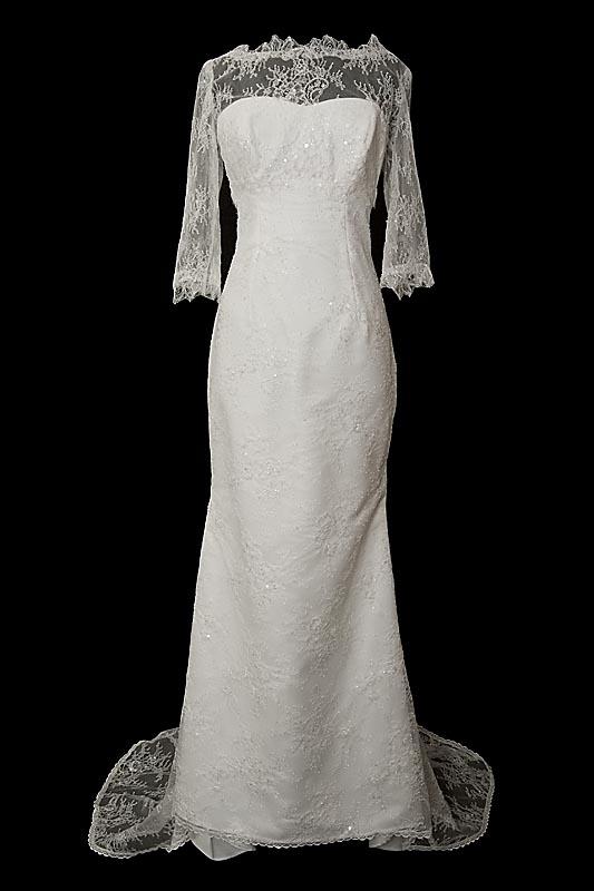 Długa koronkowa suknia ślubna Reiko z dekoltem w serduszko, rękawkami, gołymi koronkowymi plecami oraz upinanym trenem.