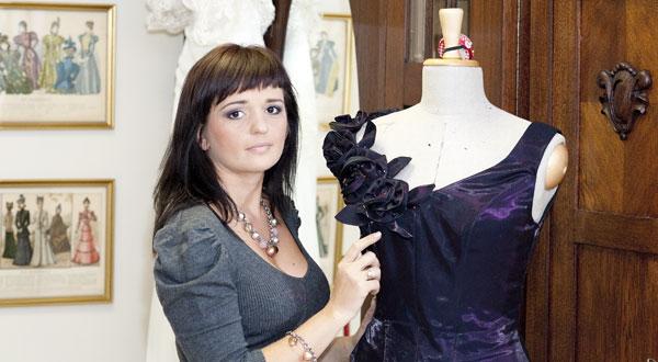 Projektantka Kama Ostaszewska w Atelier z suknią wieczorową na manekinie.
