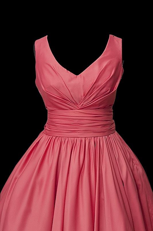 Krótka marszczona sukienka wieczorowa ze spódnicą z koła, dekoltem w literę V oraz pasem z naszytą kokardą.