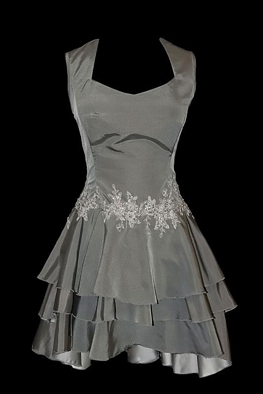 Krótka szara sukienka wieczorowa na ramiączkach z dekoltem w literę V. Na dole falbany wydłużane do tyłu, na pasie ozdobne, lekko połyskujące hafty.