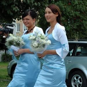 Dwie druhny w satynowych sukienkach w kolorze błękitu.