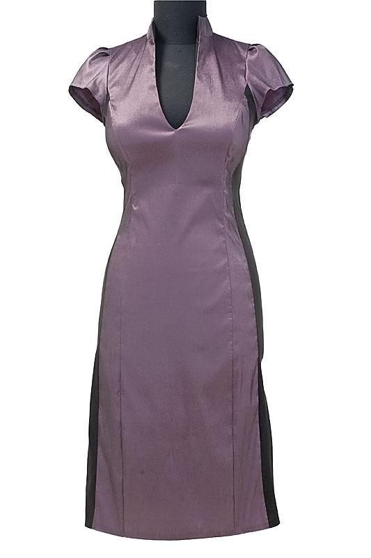 Krótka sukienka biznesowa w kolorze fioletowym z czarnymi pasami po boku, które wyszczuplają sylwetkę. Delikatny dekolt w literę V.
