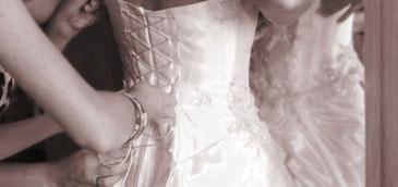 Mama wiążąca córce suknię ślubna na plecach.