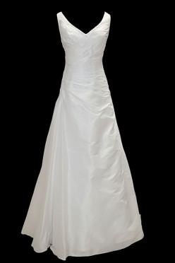 Długa prosta suknia ślubna z marszczeniami, dekoltem w szpic / literę V i gołymi plecami. Uzupełnieniem sukienki jest bolerko z długim rękawem i mankietami.