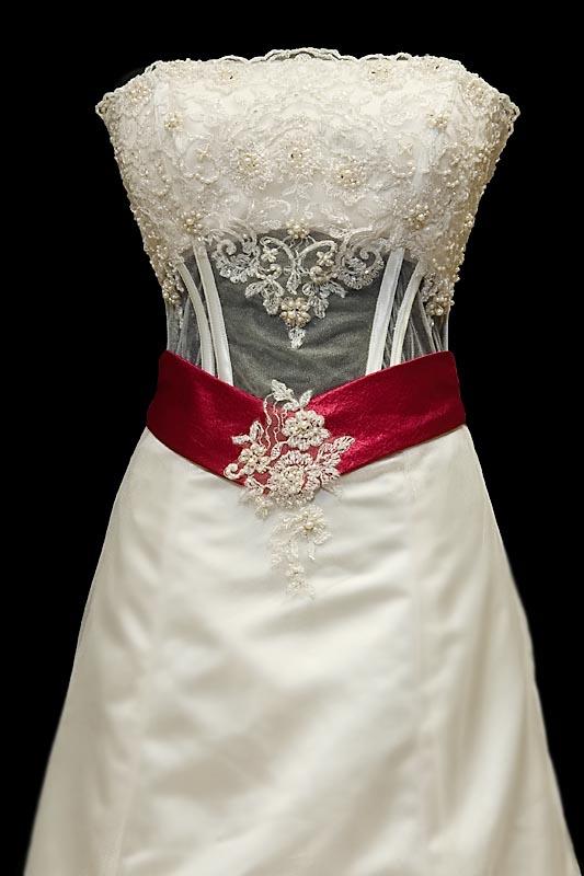 Długa wytworna suknia ślubna z koronkowym gorsetem, delikatnymi rękawkami i czerwonymi dodatkami.