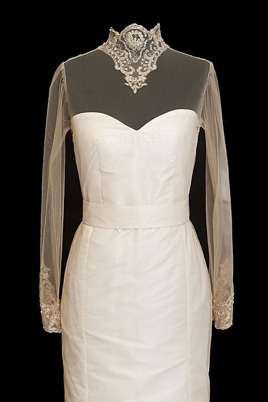 Długa suknia ślubna z odkrytymi plecami, zdobiona haftami.