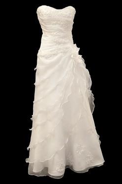 Długa suknia ślubna z koronkowym gorsetem, marszczeniami i dekoltem w serduszko oraz kwiatem. Z tyłu długi upinany tren.