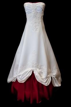 Długa suknia ślubna z koronkowymi zdobieniami i marszczeniami na gorsecie z prostym dekoltem. Sukienka z zakrytymi plecami i wiązaniami gorsetowymi.