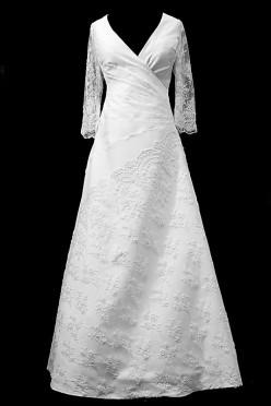 Długa suknia ślubna z portfelowym dekoltem w szpic, koronkowymi rękawkami i haftami naszywanymi na spódnicę.