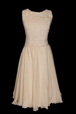 Jasna beżowa krótka suknia wieczorowa z dekoltem w łódkę i gipiurową górą.