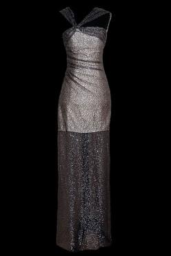 Długa czarna cekinowa suknia wieczorowa z przezroczystościami i odkrytymi ramionami i gołymi plecami.