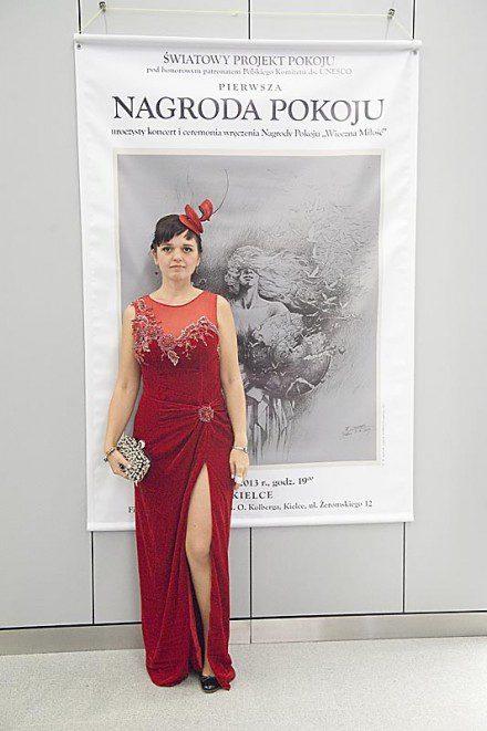 Kama Ostaszewska w czerwonej sukni i fascynatorze podczas koncertu z okazji wręczenia pierwszej polskiej Nagrody Pokoju Wieczna Miłość.