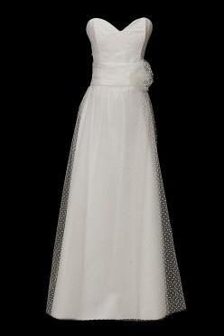 Długa suknia ślubna w groszki z dekoltem w serduszko i gołymi plecami.