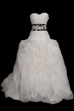 Suknia ślubna z falbanami z dekoltem w serduszko, czarnym pasem z haftami. Suknia na gorsecie z marszczeniami i spódnicą z falbanek.