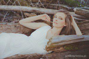 Panna Młoda s suknie ślubnej w sesji plenerowej leży na drzewie.