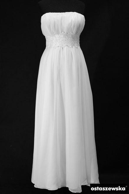 Długa suknia ślubna z marszczeniami na gorsecie z prostym dekoltem, pasem obszytym haftami i bolerkiem.