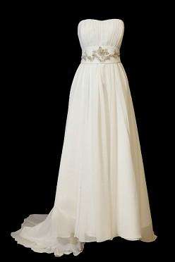 Długa suknia ślubna odcinana w pasie o kroju w literę A. Greczynka z odpinanym trenem, zakrytymi plecami i dekoltem w serduszko.