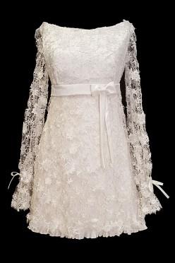Krótka koronkowa sukienka ślubna z długimi koronkowymi rękawkami i kokardkami.