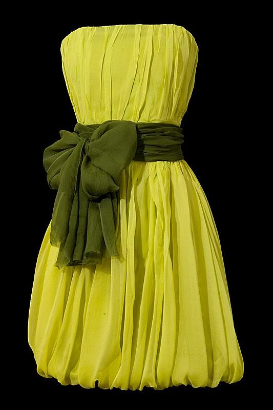 Zielona marszczona sukienka na wesele z zielonym pasem i kokardą z przodu.