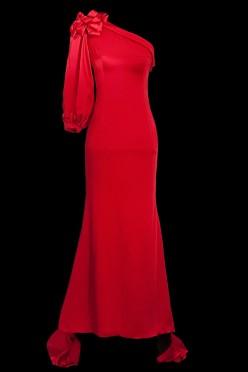 Długa elegancka czerwona suknia wieczorowa z rękawem i odkrytym ramieniem i podpinanym trenem.