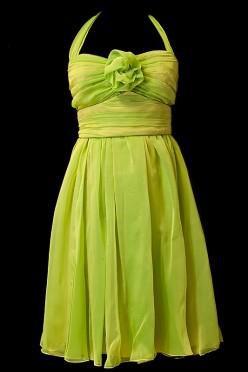 Krótka zielona suknia wieczorowa z marszczeniami, pasem i kwiatem na dekolcie.