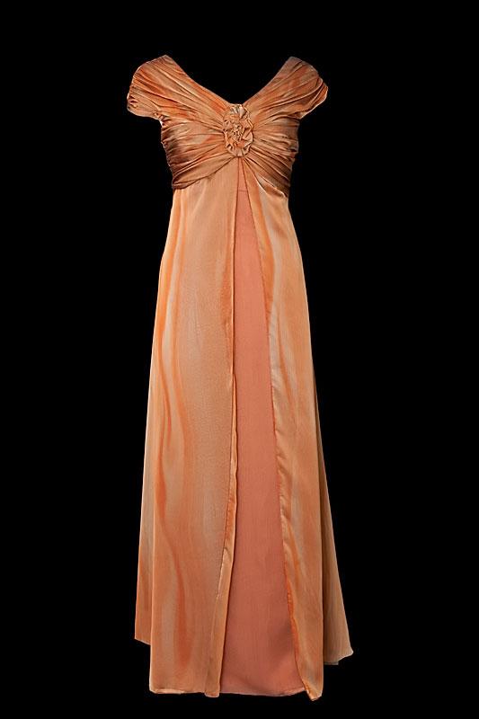 Wytworna i elegancka suknia wieczorowa z marszczeniami i ręcznie robionym kwiatem.