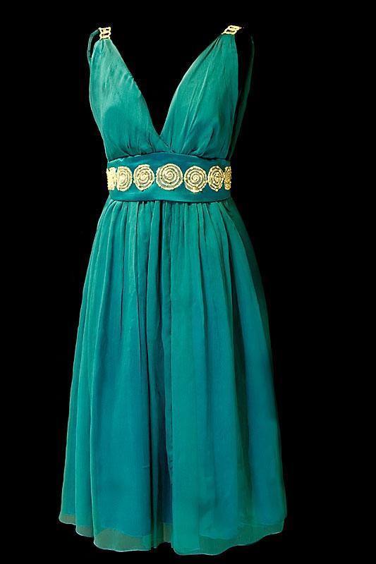 Krótka suknia wieczorowa z jedwabiu w kolorze szmaragdowym z szerokim zdobionym pasem oraz głębokim dekoltem w literę V i wycięciem na plecach.