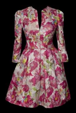 Krótka suknia wizytowa w kwiaty z długim rękawem.